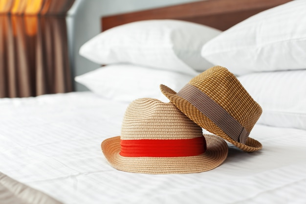 Vacation hat on the bed in hotel. Premium Photo