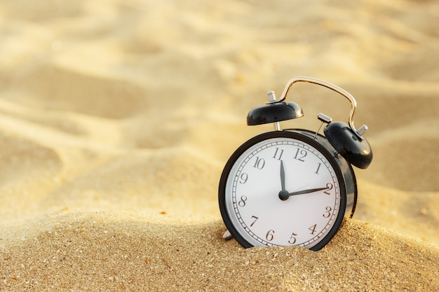 Vacation time, alarm clock on the sand Premium Photo