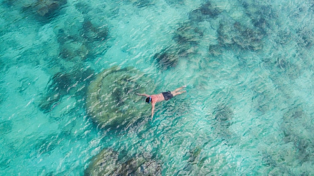 Vacation tourist snorkel man swimming snorkeling in paradise clear water. swim boy snorkeler in crystalline waters and coral reefs. turquoise ocean background. Premium Photo