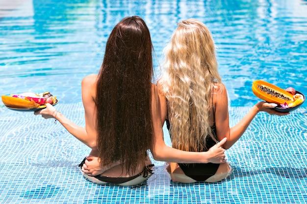 エキゾチックなフルーツのプレートを保持しているプールでポーズ不足のビキニを着て、カメラに戻って座っている驚くべき長いブロンドとブルネットの髪を持つ2人の遅い女の子への休暇トロピカルポートレート、 無料写真