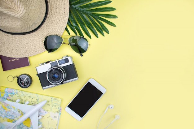 Vacation with a hat, map, smartphone, film camera and sunglasses on a yellow background. top view. Premium Photo