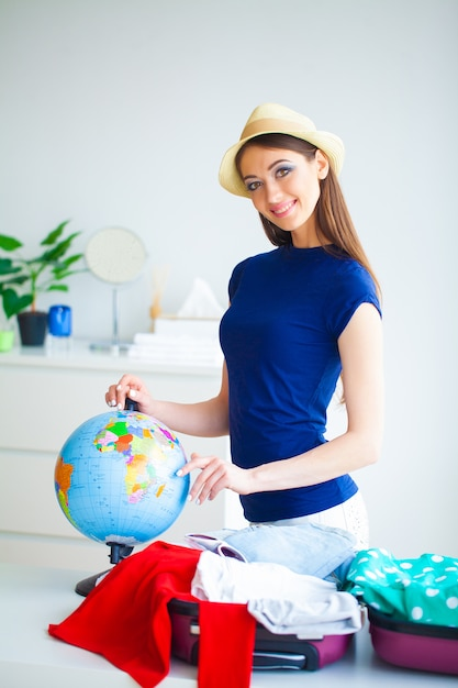 Vacation. woman who is preparing for rest. young beautiful girl sits on the bed. portrait of a smiling woman. happy girl goes on vacation Premium Photo
