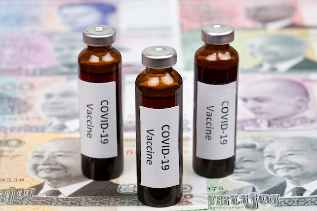 Vaccine against covid-19 on the background of cambodian riel Premium Photo
