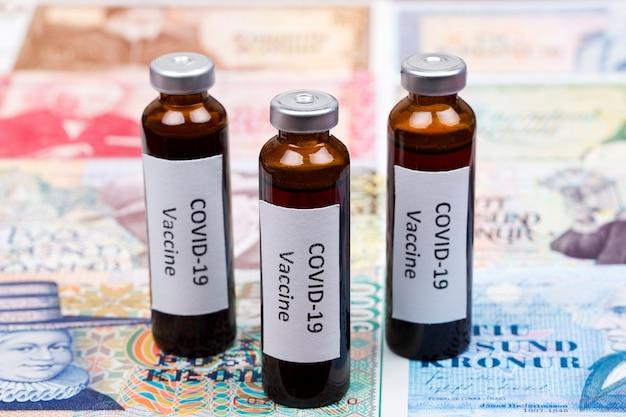 Vaccine against covid-19 on the background of icelandic krona Premium Photo