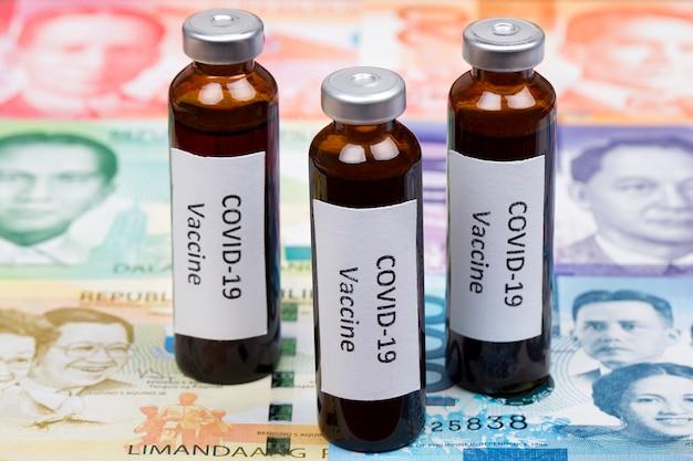 Vaccine against covid-19 on the background of philippine peso Premium Photo