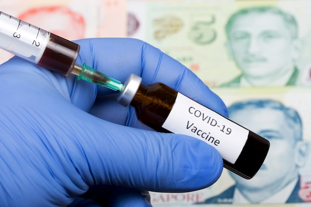 Vaccine against covid-19 on the background of singapore dollar Premium Photo
