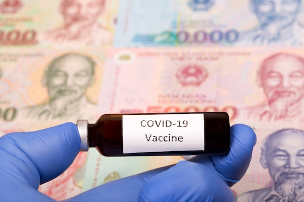 Vaccine against covid-19 on the background of vietnamese money Premium Photo