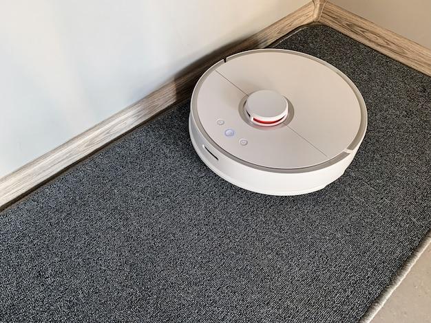 Vacuum cleaner robot runs on floor in a living room  Photo