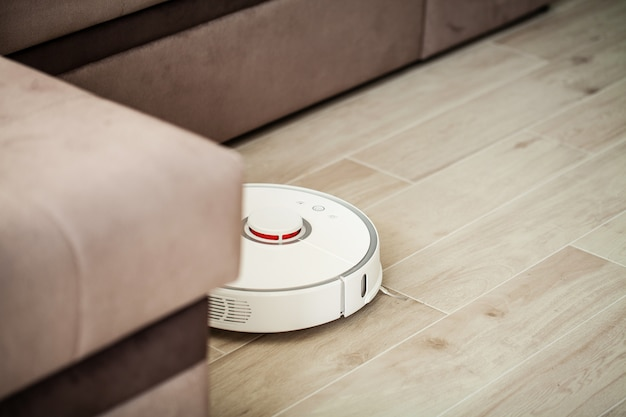 Vacuum cleaner robot runs on wood floor in a living room, Premium Photo