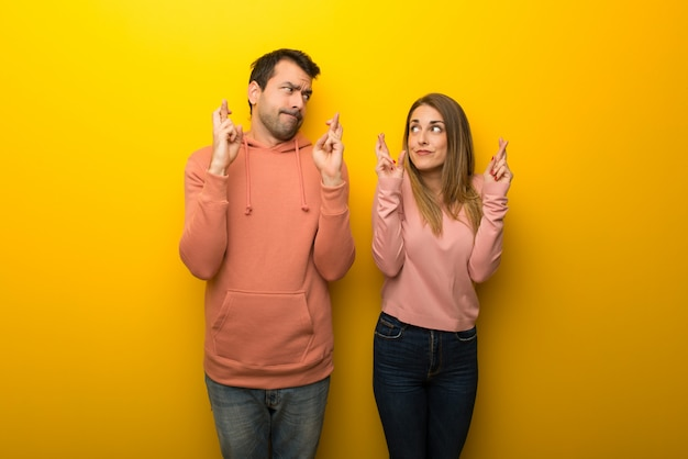In valentine day group of two people on yellow background with fingers crossing and wishing the best Premium Photo