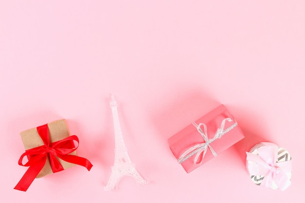Valentine day layout. gifts, hearts, eiffel tower on a pink pastel background. st. valentines day Premium Photo