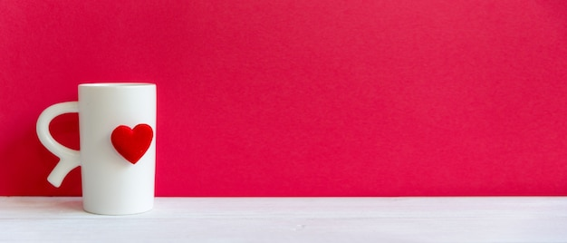 Valentine day with white cup coffee red heart on the cup, red wall background, copy space and banner for text.  valentine concept. Premium Photo