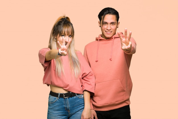 In valentine day young couple happy and counting three with fingers over pink background Premium Photo