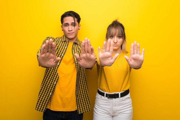 In valentine day young couple over vibrant yellow background making stop gesture for disappointed with an opinion Premium Photo
