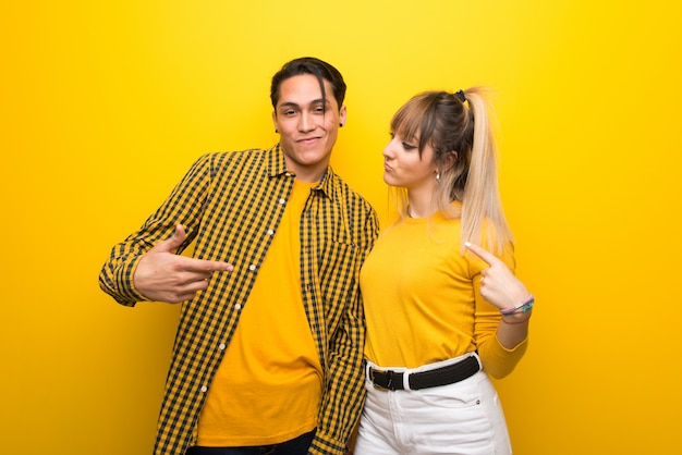 In valentine day young couple over vibrant yellow background proud and self-satisfied in love yourself concept Premium Photo