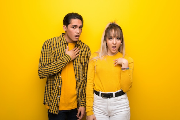 In valentine day young couple over vibrant yellow background surprised and shocked while looking right Premium Photo