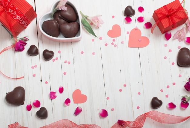 バレンタインギフトボックスと白い木の板に赤いハート Premium写真