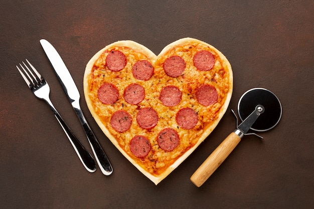 Valentine's day arrangement with heart shaped pizza and tableware Free Photo