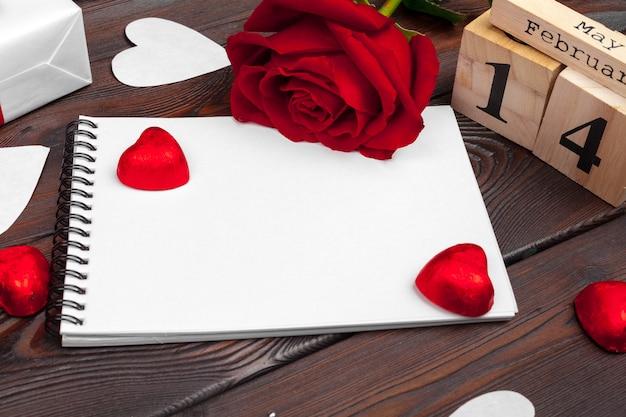 バレンタインデーの背景。空の空白のノートブック、ギフトボックス、白地に花、トップビュー。テキスト用の空き容量 Premium写真