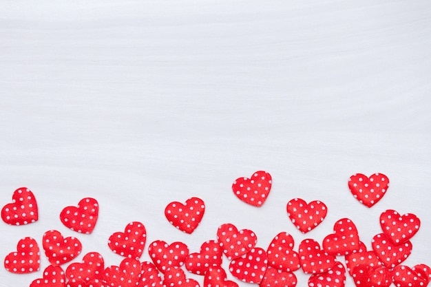 Valentine's day background. red hearts on white wooden background. valentines day, love, wedding concept. flat lay, top view. Premium Photo