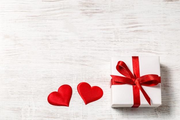 Предпосылка дня валентинки с подарком и красными сердцами, взглядом сверху. сан валентин и понятие любви. Premium Фотографии