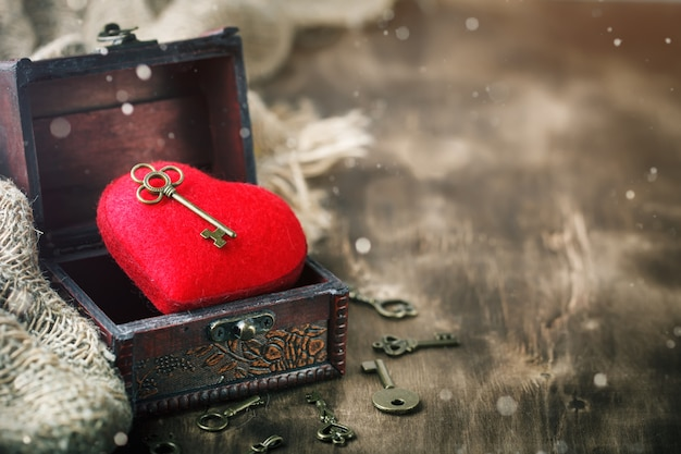 Valentine's day background with a heart and an ancient key on wooden table. Premium Photo