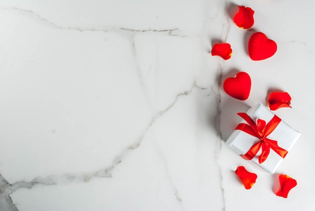 Valentine's day background with rose flower petals, white wrapped gift box with red ribbon and holiday red candle, on white marble background, copy space top view Premium Photo