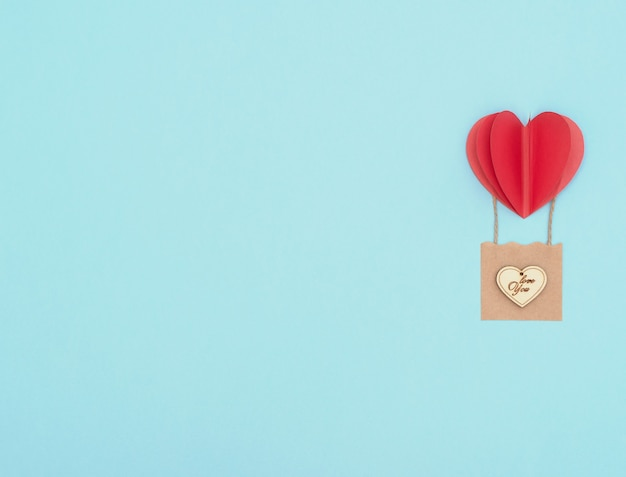 バレンタインデーの青い背景に赤いハートの風船、木製のハートが付いたクラフトバスケット。 Premium写真
