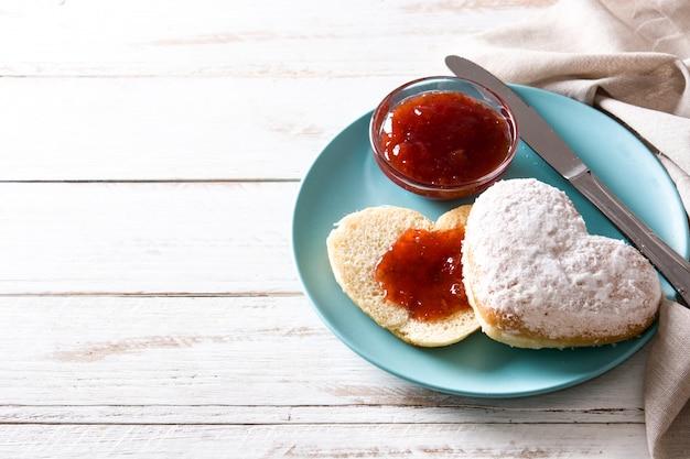 Valentine's day breakfast heart-shaped bun and berry jam, copy space Premium Photo