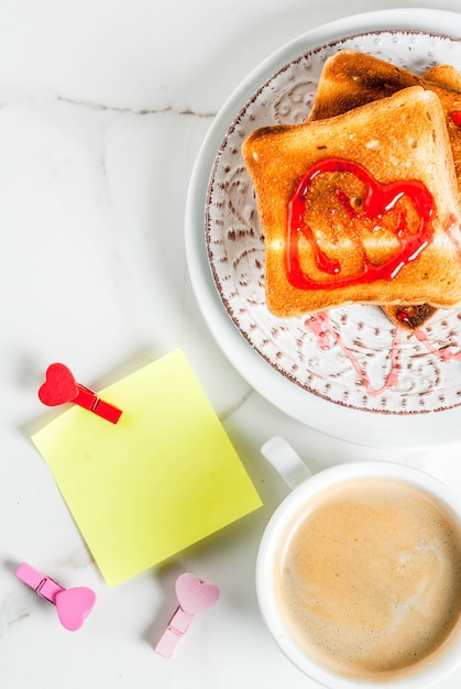 Valentine's day breakfast idea with coffee mug, toasted bread with red strawberry jam, blank paper note for congratulations with heart shaped pins, white marble background, copy space top view Premium Photo