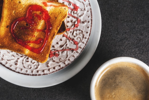Valentine's day breakfast idea with coffee mug, toasted bread with red strawberry jam Premium Photo