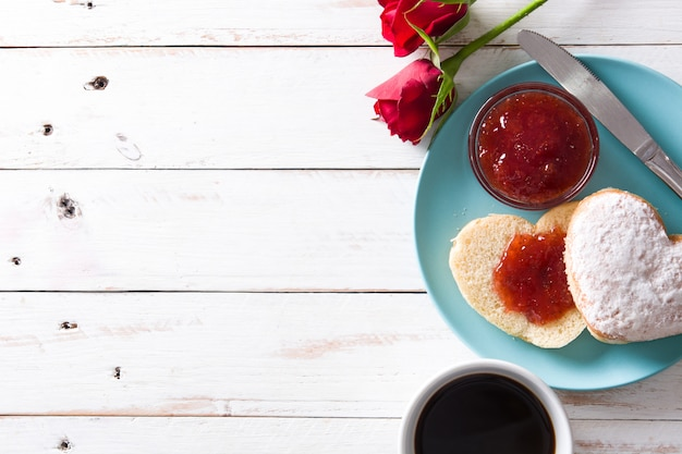 Valentine's day breakfast with coffee, heart-shaped bun, berry jam and roses Premium Photo