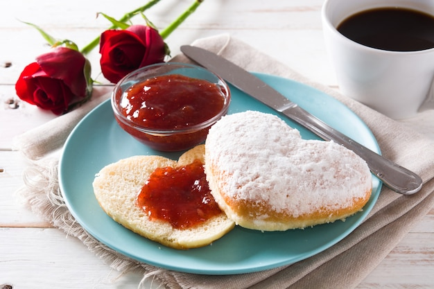 Valentine's day breakfast with coffee, heart-shaped bun and berry jam. Premium Photo