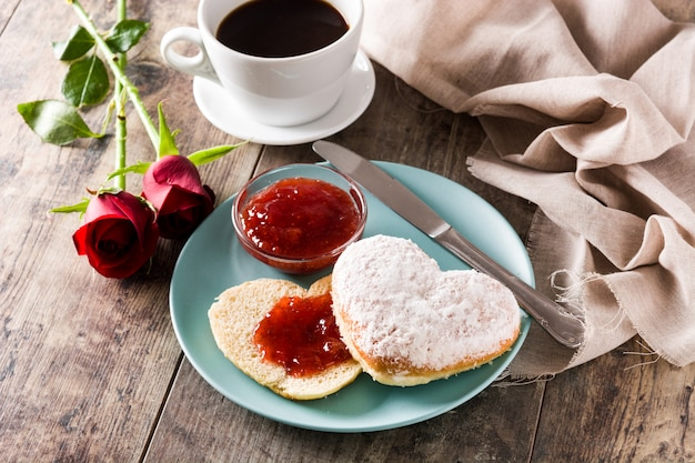 Valentine's day breakfast with coffee heart-shaped bun and berry jam Premium Photo