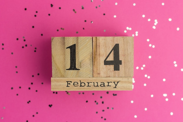 Valentine's day on calendar. february 14. pink background with multicolored confetti. flat lay style Premium Photo