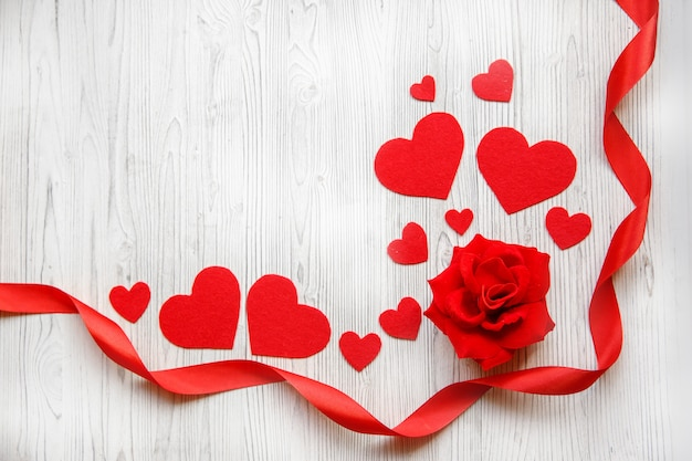 Valentine's day card, red hearts, ribbon and red rose on a white wooden background. space for text Premium Photo
