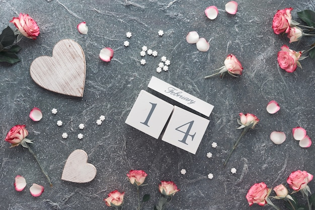 Valentine's day celebration, flat lay with wooden calendar, pink roses and wooden hearts Premium Photo