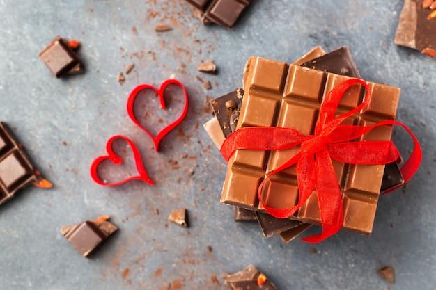 バレンタイン・デー。チョコレートバーは赤いリボンとハートを飾りました。上面図 Premium写真