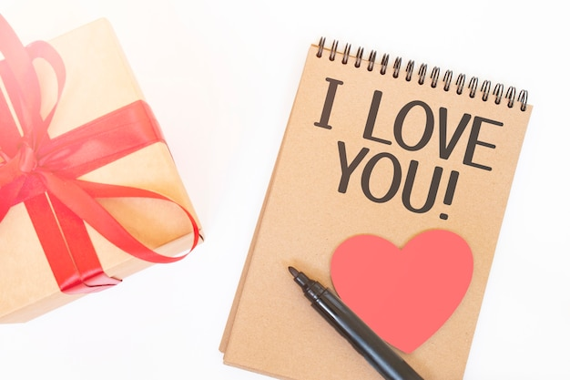 Концепция дня святого валентина. подарочная коробка creaft с красной лентой, розовым деревянным сердцем, черным маркером и цветной блокнот с надписью i love you Premium Фотографии