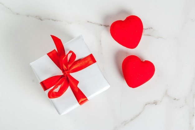 Valentine's day concept, white wrapped gift box with red ribbon and red velvet hearts, on white marble background, copy space top view Premium Photo