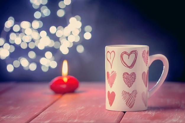빛나는 배경 위에 뜨거운 음료 한잔과 함께 발렌타인 개념 프리미엄 사진