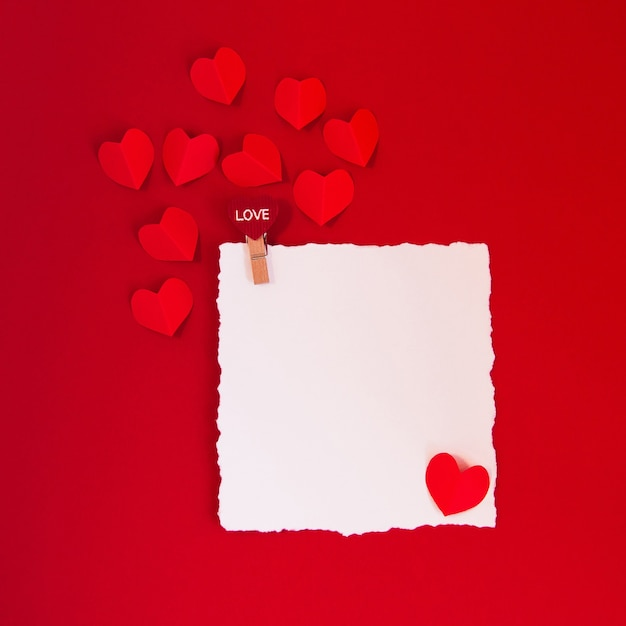 Valentine's day concept with red hearts on red background and white card for text,  flat lay, copy space Premium Photo