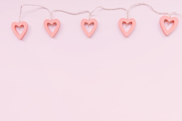 Valentine's day decoration - heart shaped lights on a pink background Premium Photo