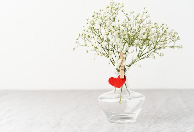 Valentine's day. delicate white flowers in vase. red felt heart - symbol of lovers Premium Photo