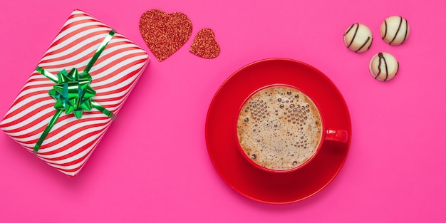 Valentine's day or the feast of saint valentine concept. gift and foam latte, red hearts and white chocolate candies. romantic pink card. a red cup and saucer with hot drink in the morning. Premium Photo