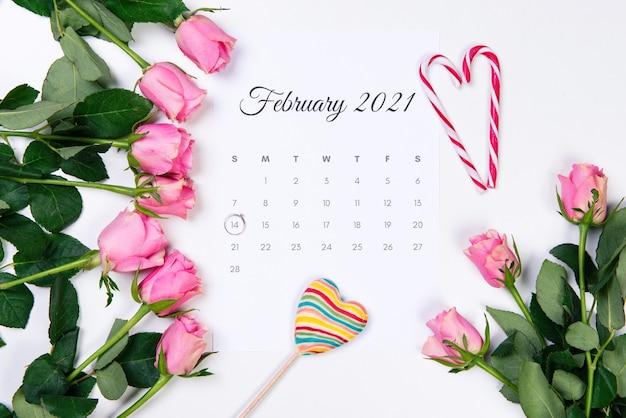 バレンタインデーの2月のカレンダー、ダイヤモンドリング、ハート、白い背景にピンクのバラ。 Premium写真