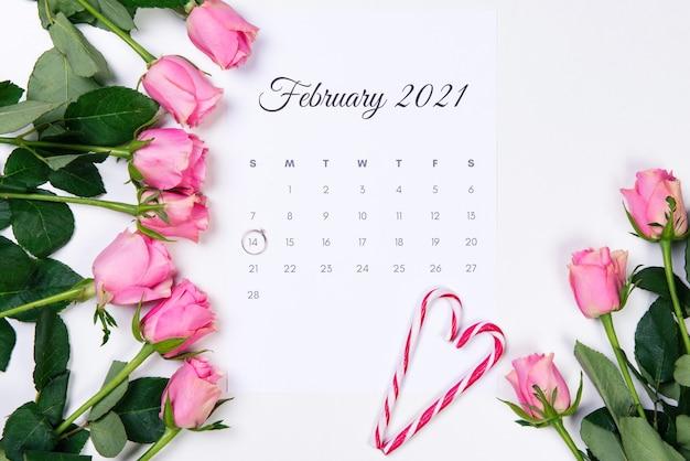 バレンタインデーの2月のカレンダー、ダイヤモンドの指輪、赤いハート、白い背景にピンクのバラ。 Premium写真