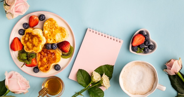 Valentine's day flat lay with heart shaped pancakes on a blue. valentine's day concept. view from above. banner Premium Photo