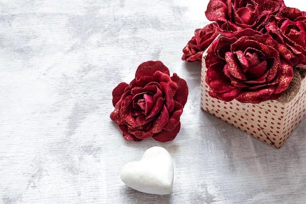 明るい背景のコピースペースに装飾的なバラと白いハートのバレンタインデーのギフト。 無料写真