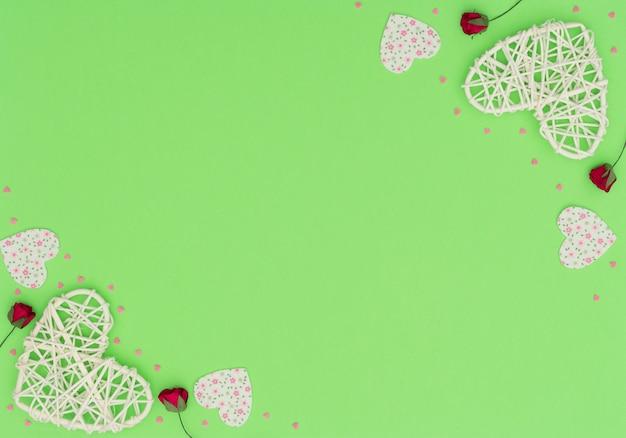 등나무와 펠트 하트, 빨간 장미와 작은 핑크 하트와 함께 발렌타인 데이 녹색. 프리미엄 사진
